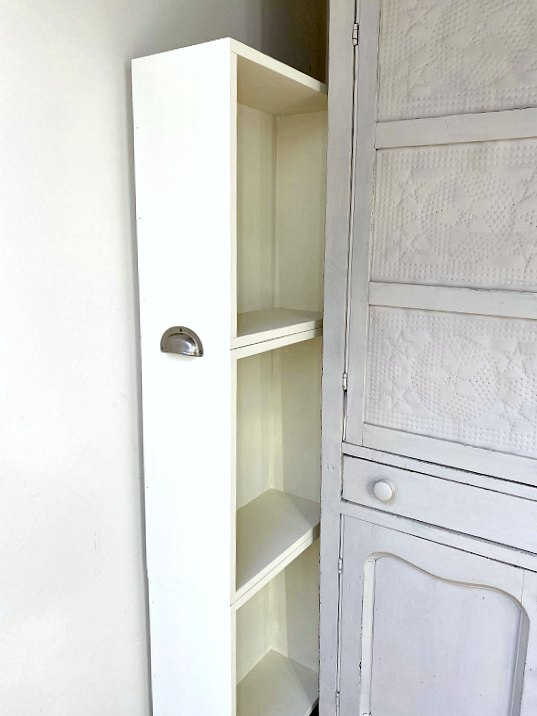 Painted storage between wall and hutch with cup pull