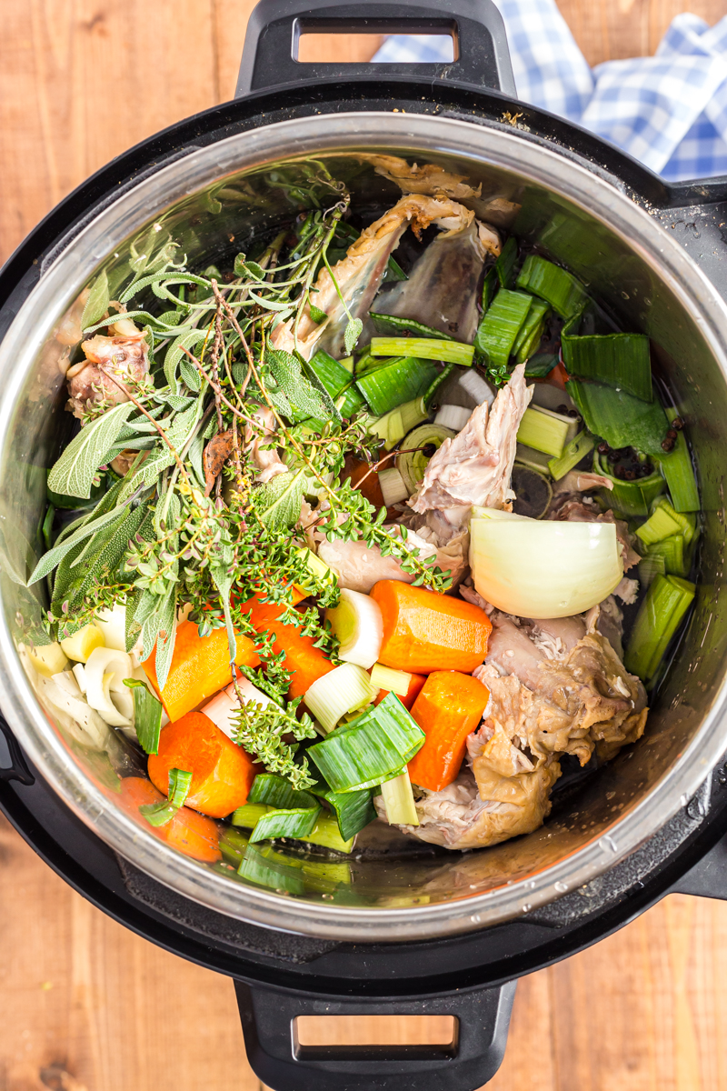 View of ingredients for homemade turkey bone broth inside the Instant Pot.