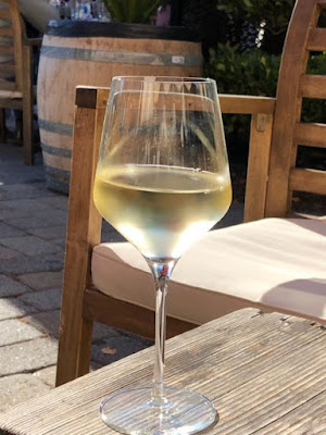 A glass of white wine on a table.