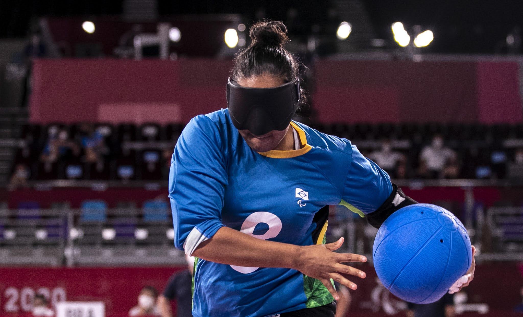A jogadora Jéssica Gomes, que é morena, está vestida de azul e com o número 8 no centro da camisa está de pé com a bola do jogo, também azul, na sua mão esquerda. Ela usa uma venda preta na cabeça.