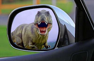 A Tyrannosaurus Rex is reflected in a car's driver's side-view mirror.