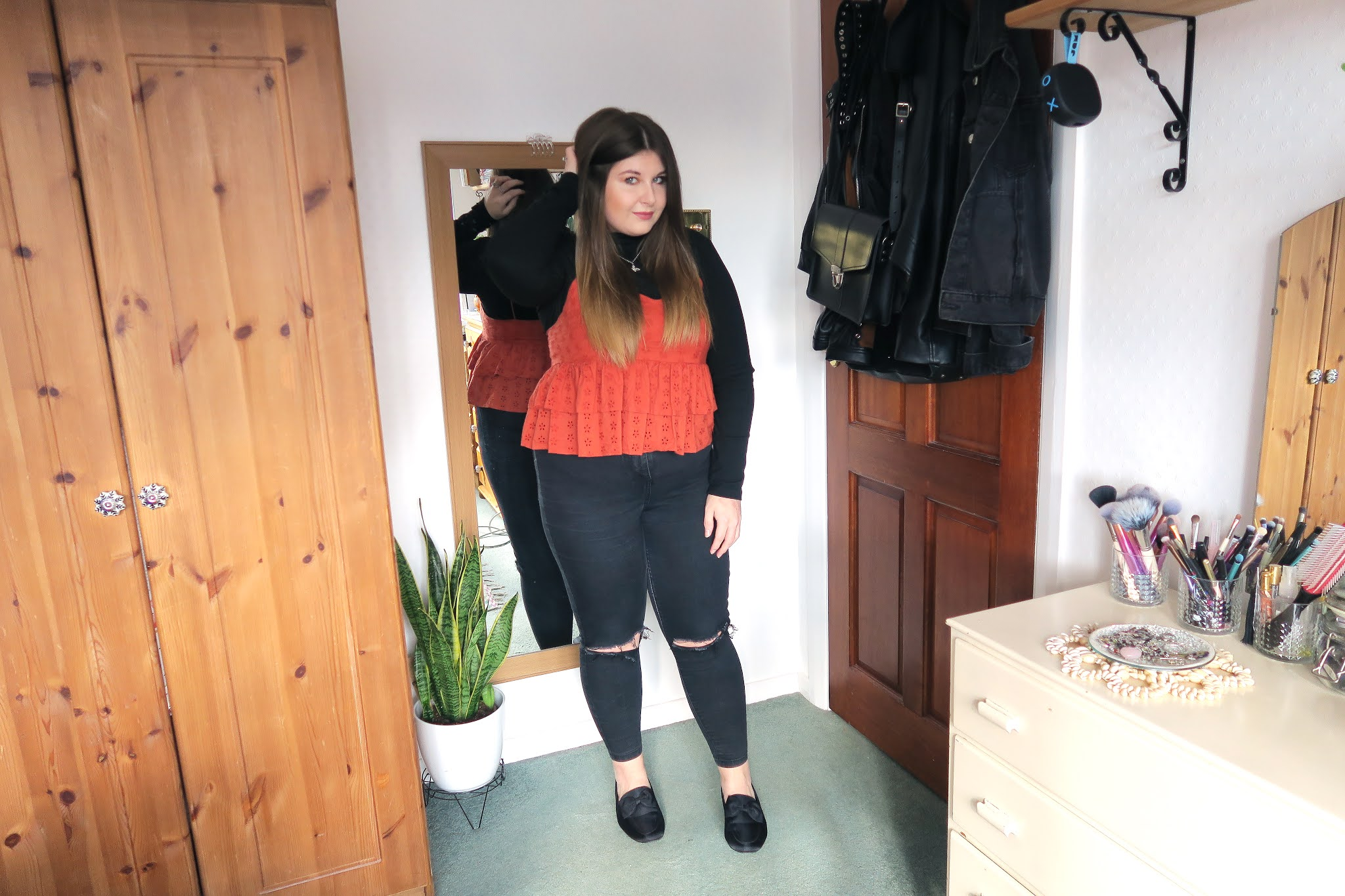 Grace is wearing a plain black roll neck top underneath a burnt orange spaghetti strap vest. She is also wearing a pair of black ripped skinny jeans and a pair of black shoes