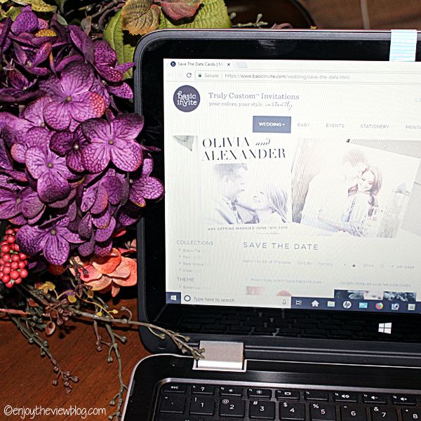Laptop computer sitting on a table (with flowers in the background) with the browser open to the Basic Invite save-the-date page