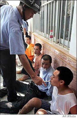 A Chinese police officer lights an inmate's last cigarette.