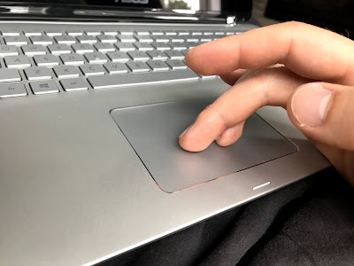 Two fingers on a laptop trackpad using the scroll gesture