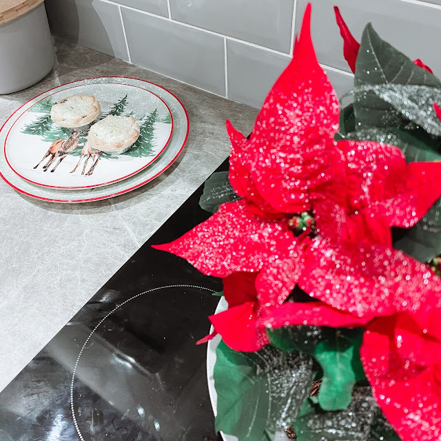 A Christmas poinsettia, Christmas plates with two mince pies on top