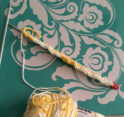 A mix of white and yellow stitches on a knitting needle, with a ball of white and yellow yarn visible at the bottom edge