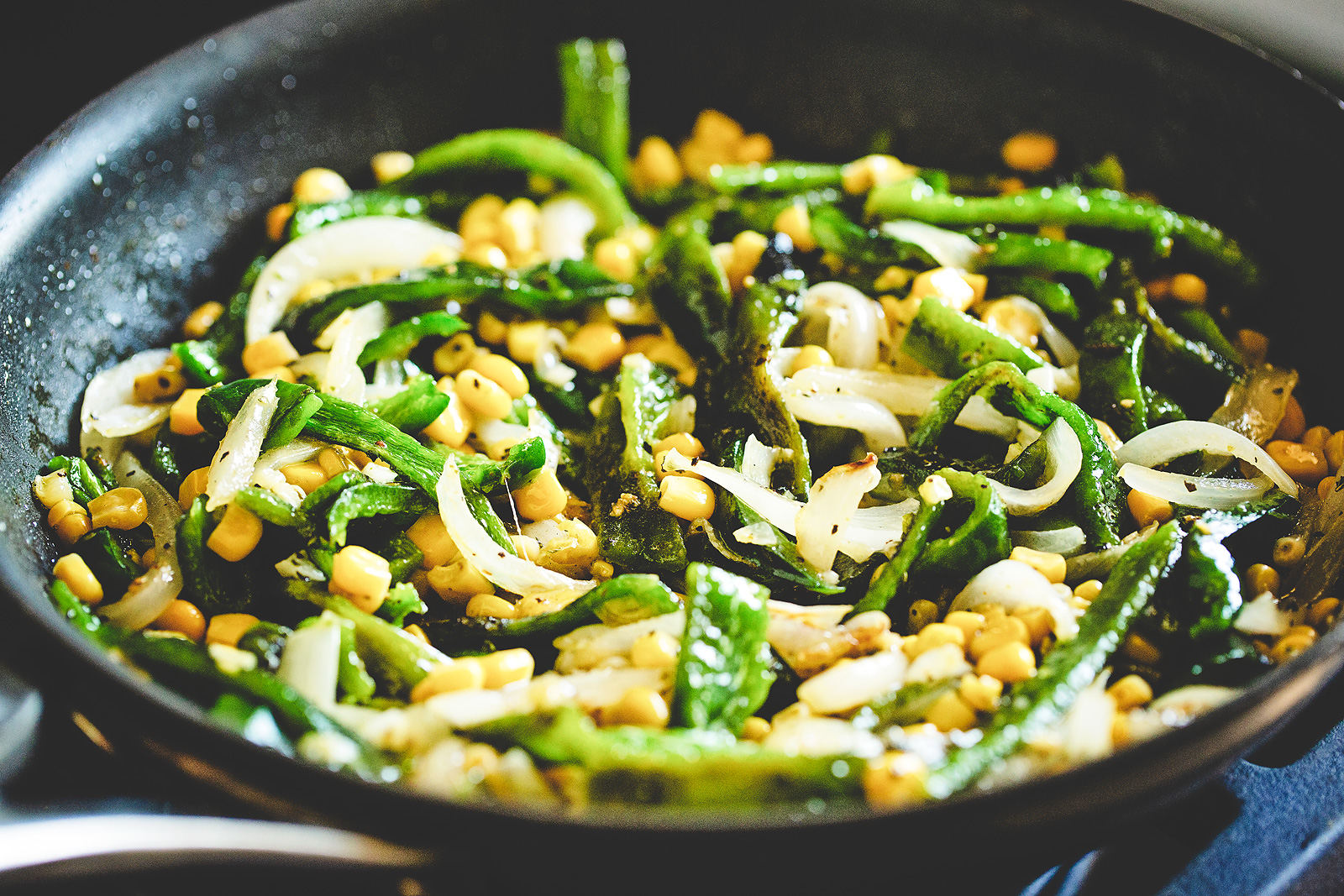 Skillet on the stove with veg and spices.