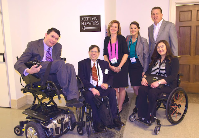 Two manual wheelchair users, a power wheelchair user, and three able bodied people, pose for a picture in a hallway of the House of Representatives. The power wheelchair user has elevated his seat