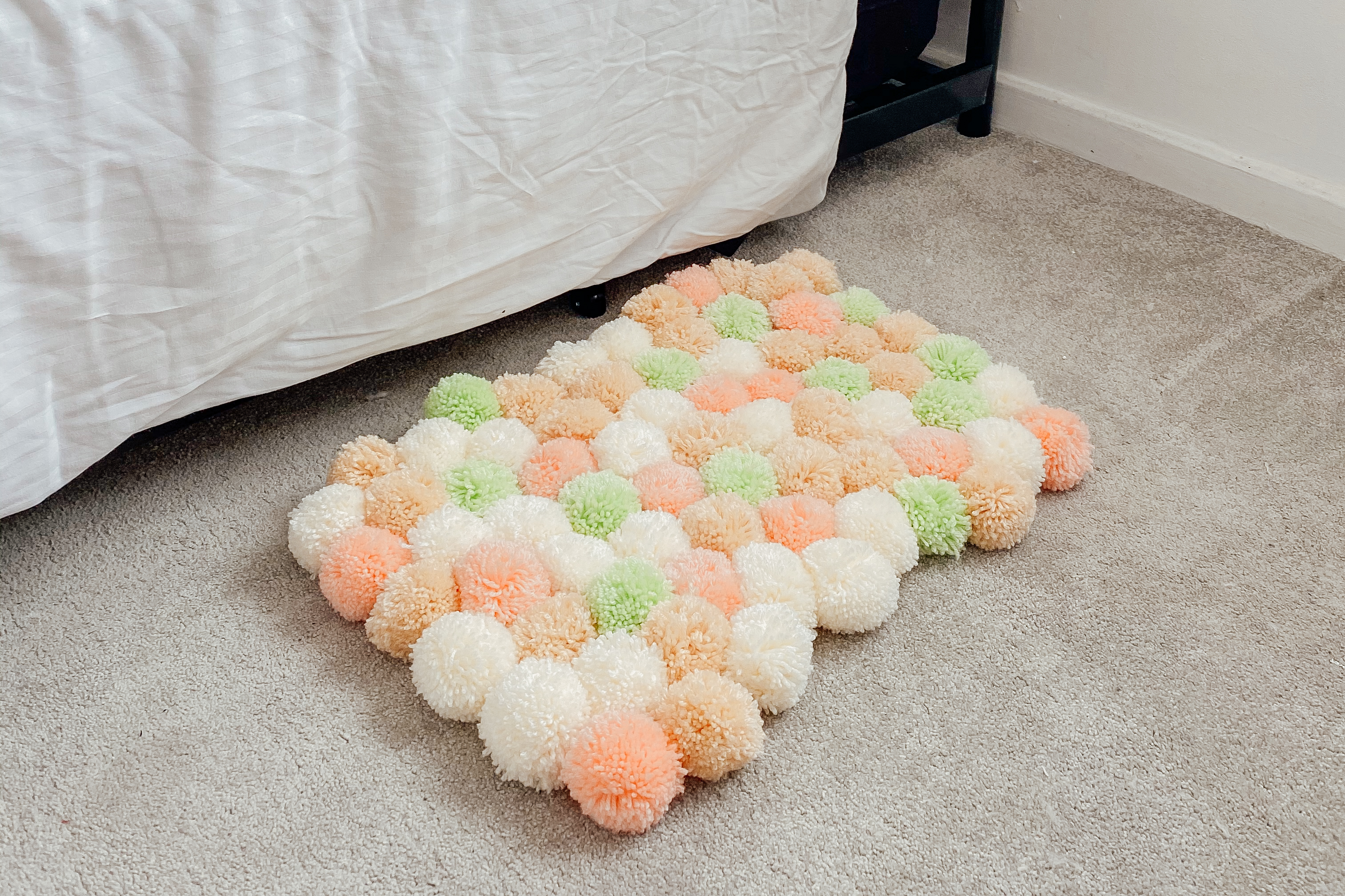 Pom-pom rug next to a bed