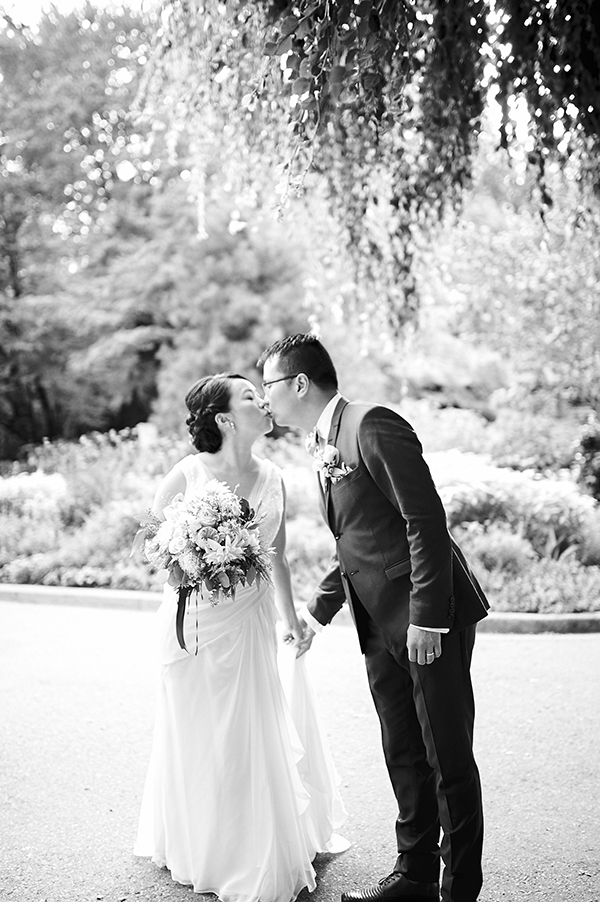 Bride and groom kiss. Vancouver-based beauty, life and style blogger in a David's Bridal wedding gown in Stanley Park, Vancouver, Canada; bridal bouquet by Flower Factory