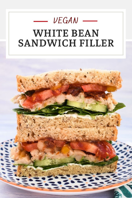 A vegan Italian white bean and tomato sandwich stacked high with a white bean sandwich filler, salad and a tangy dressing. Good for lunches are home or lunch boxes.