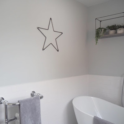 A simple metal star adding interest and personality to the bathroom walls