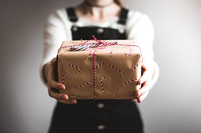 A person in black overalls and a white shirt holds a present. It's wrapped in brown wrapping paper, decorated with red and white candy canes. A red and white string is tied around the present.