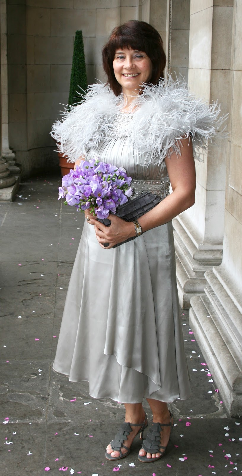 A second wedding dress is freed from the constraints that a first wedding imposes. Here Gail Hanlon wears a silver dress from Monsoon with feather boa. June 2010