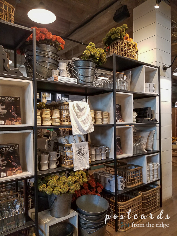 shelves with mugs, pillows, books, and buckets at Magnolia market