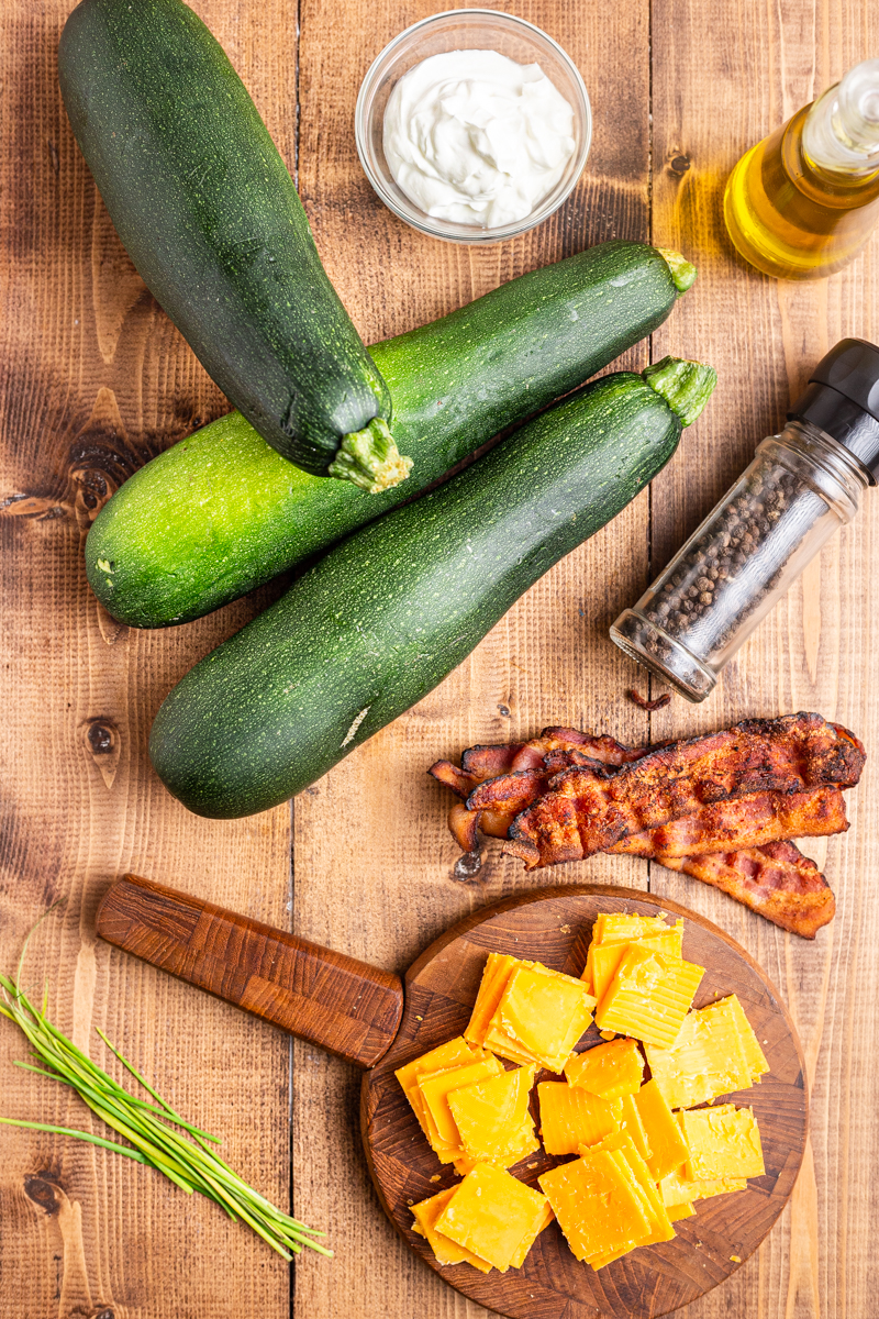 Overhead photo of the ingredients needed to make Hasselback Zucchini on a wooden table.