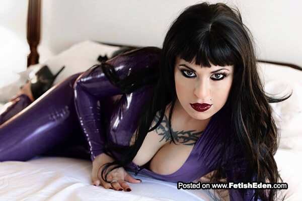 Brunette with tattoo wears purple latex catsuit
