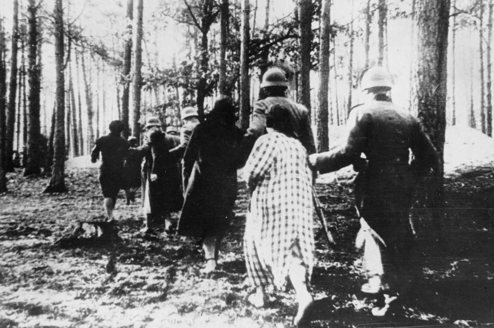 Polish women are led through woods to their executions by German soldiers sometime in 1941.
