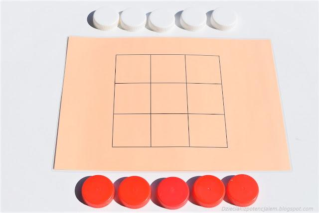 na zdjęciu widać planszę w kolorze pomarańczowym do gry w kółko i krzyżyk, obok planszy leżą dwa zestawy nakrętek służących za pionki