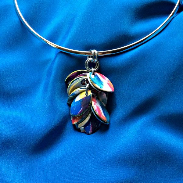 colorful pendant composed of petal shapes dangling on curved silver necklace