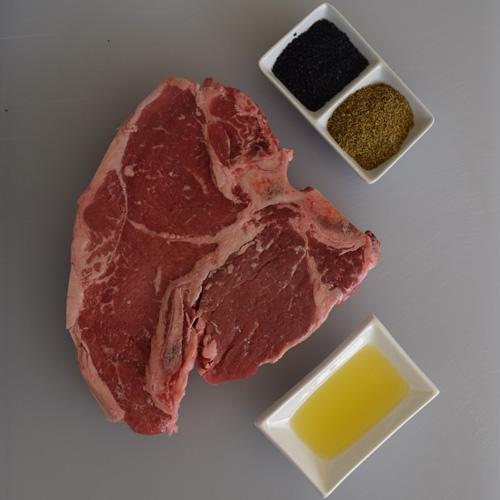 Porterhouse steak with black salt and green peppercorns