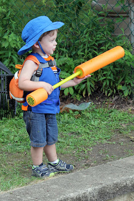 Boy with a water gun wearing a cool kids toddler cooling vest