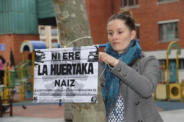 Una de las activistas de La Huertaka coloca un cartel en Herriko Plaza