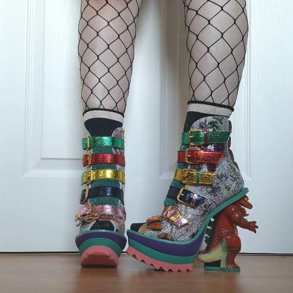 legs wearing dinosaur heeled boots in floral patent with metallic and glitter details
