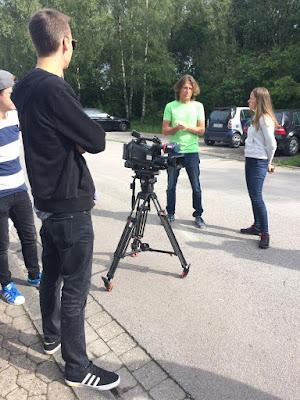 Das Team des WDR steht im Kreis und bespricht sich. In der Mitte die Kamera auf einem Stativ.