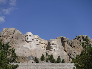 the four heads carved into Mount Rushmore are centered above a gray brick wall and some dark green pine branches, with a bright blue sky in the background