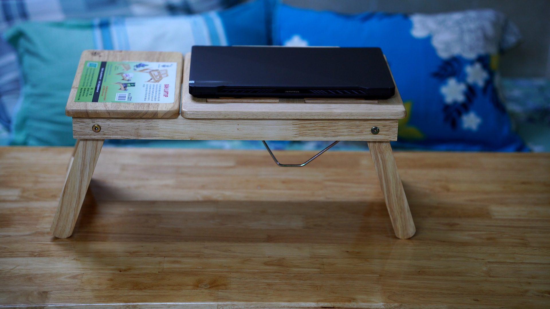 Trên tay bàn gỗ mini để máy tính laptop gấp gọn