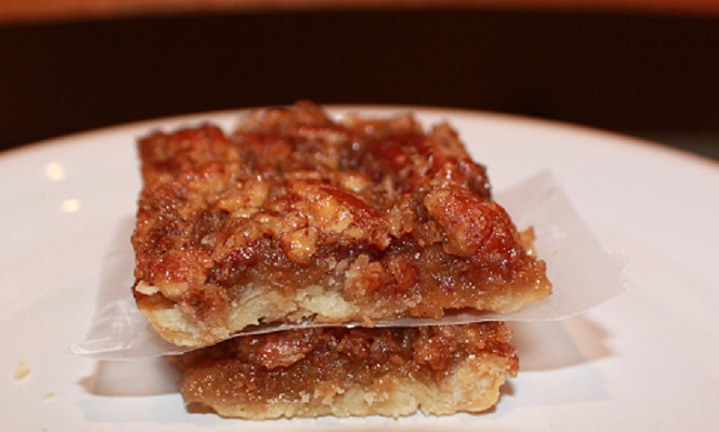 these are two pecan pie bars on a white plate with a black background that taste like a pecan pie in a bar form