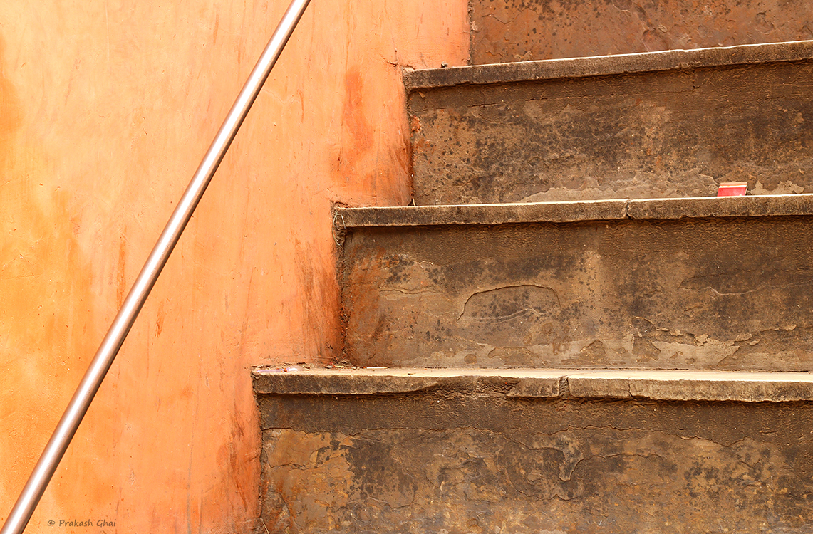 A minimalist photo of an orange colored Ascending Staircase