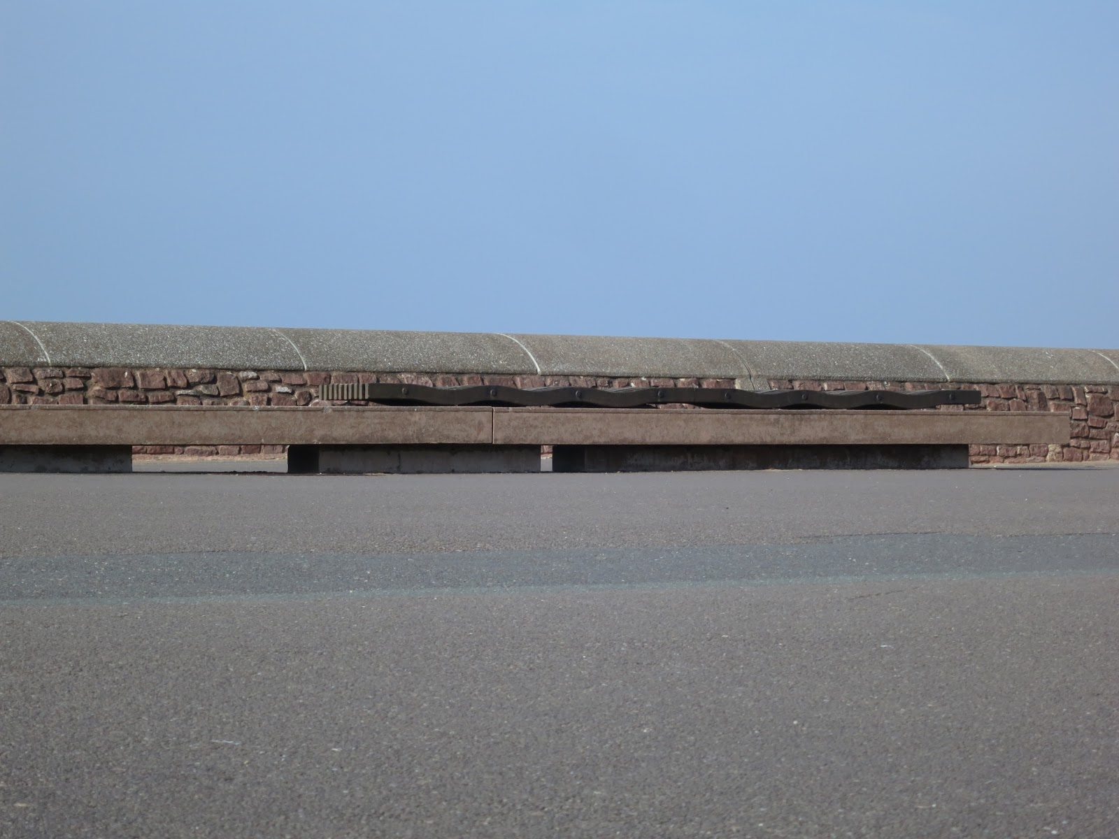 Long sea wall with bench against it between pavement and cloudless blue sky.