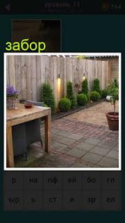 сделан глухой забор рядом с которым стоит стол и ваза с растением
