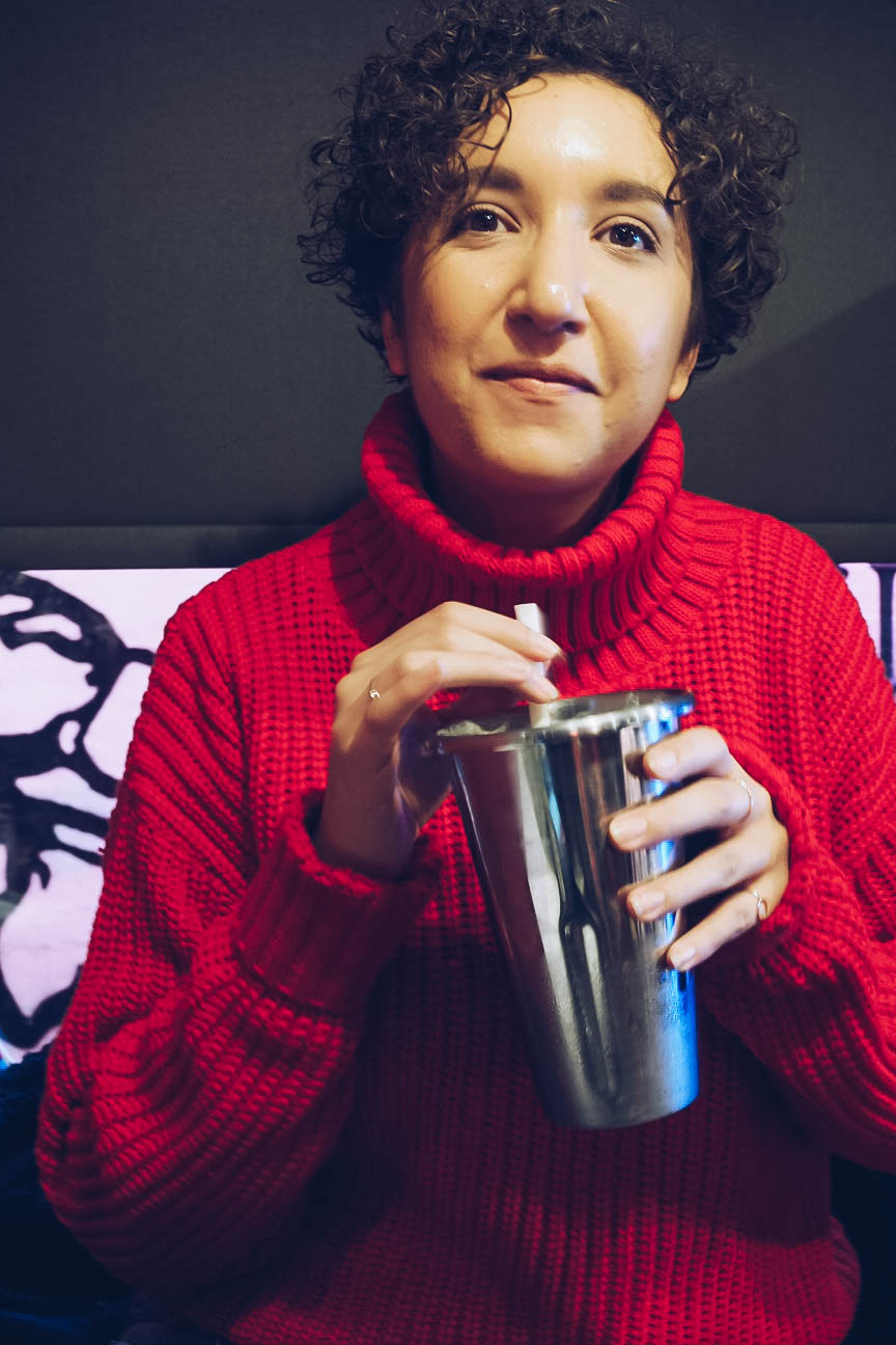 Woman wearing a red jumper and drinking milkshake