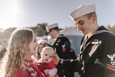 Military Sailor meeting baby for the first time at Naval Base Point Loma, California . Images by Morning Owl Fine Art Photography.