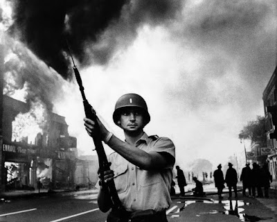 July 1967, Michigan National Guardsman stands at the ready as firefighters  battle one of numerous blazes in riot-torn Detroit (AP Photo)
