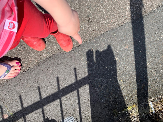 A toddler pointing at a shadow from railings that looks like a cat waving