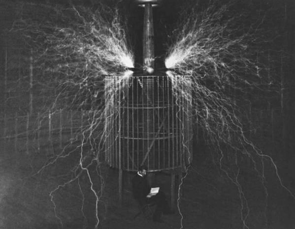 Un brillo de nitrógeno llena la atmósfera. Tesla es fotografiado sentado en frente de su generador. Esta fotografía fue tomada en 1899.