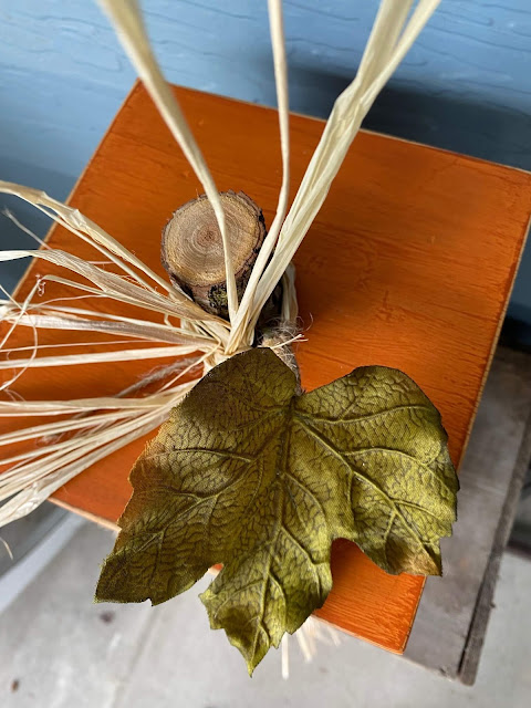 Photo of a tree branch pumpkin stem with silk leaf and raffia