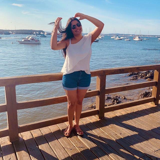 mulher morena de blusa branca, short jeans em frente a uma região de porto de embarcação