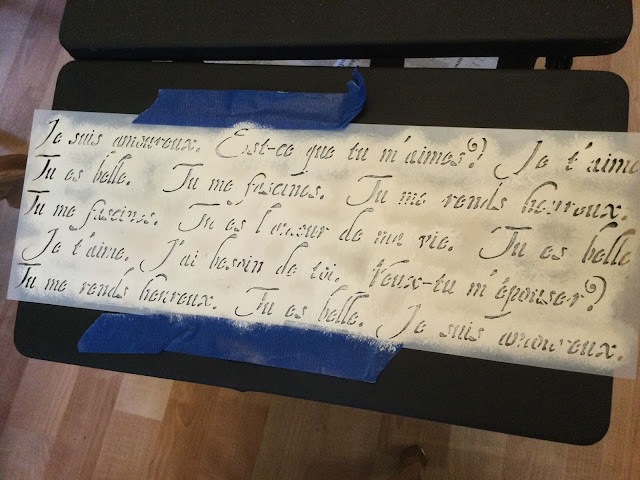 Photo of a typing table being stenciled with a French Script stencil