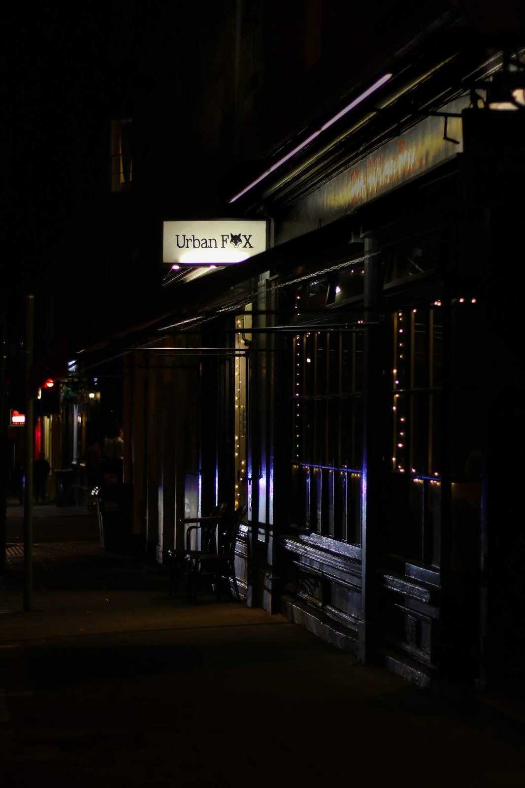 Street photo of the outside of Urban fox restaurant in Edinburgh. It's at night, the photo is quite dark with some light coming from the window and the sign as well as cars passing by.