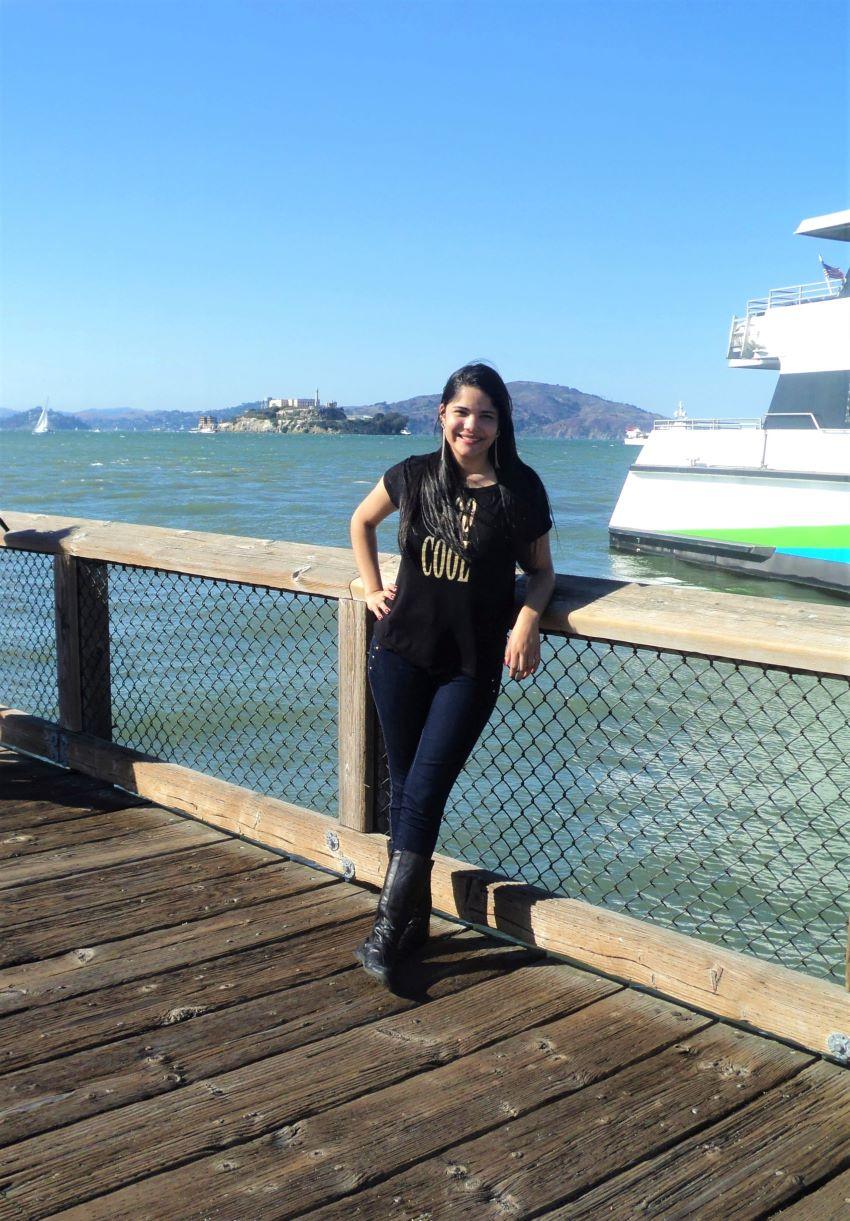 mulher jovem no porto de São Francisco com a prisão de alcatraz ao fundo
