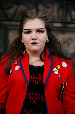 Photo of a girl in punk make up wearing a red blazer