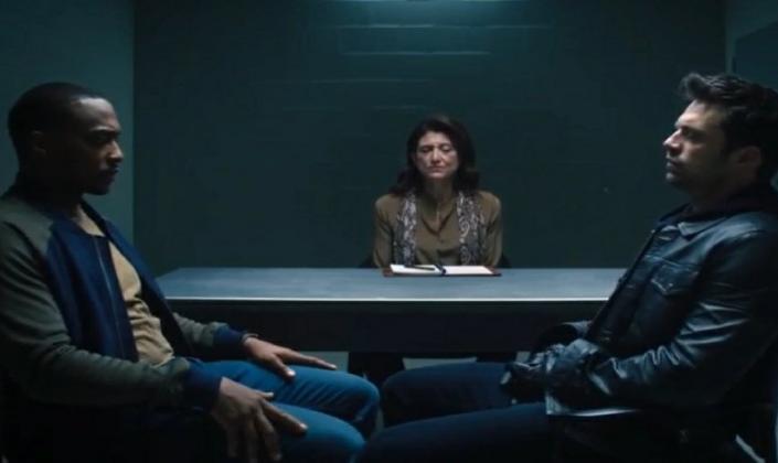 Imagem de capa: os personagens Sam e Bucky, em suas roupas de civil e sentados em um par de cadeiras encarando um ao outro e no centro a terapeuta sentada na mesa e observando os dois com uma pasta em sua frente.