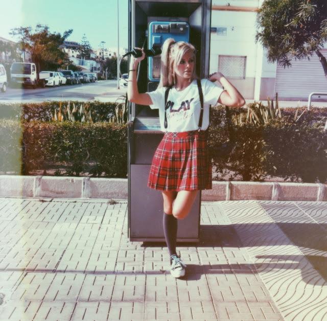 Alejandra Colomera vestida con camiseta blanca con mensaje, falda de tablas cuadros escoceses, tirantes, calcetas y zapatillas con cabina de teléfono