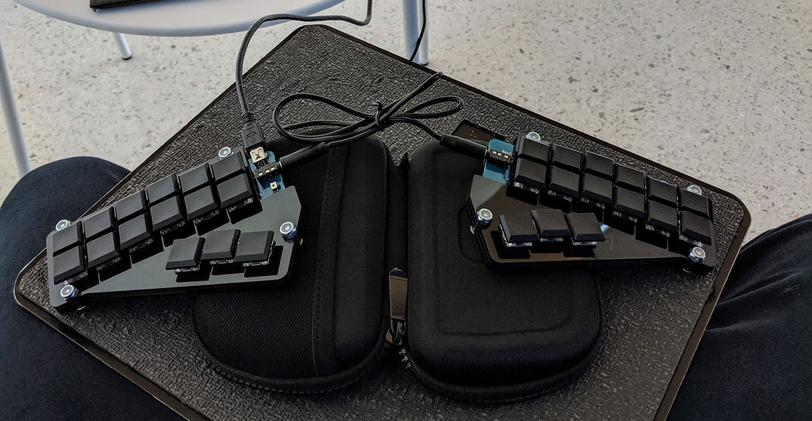 A Georgi keyboard resting on a laptop tripod with a Polarpro Osmo Pocket case propping up each side